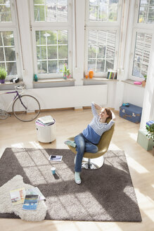 Relaxed woman at home sitting in chair - RBF004582