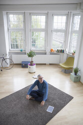 Relaxed mature man at home sitting on floor - RBF004588