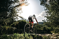 Mountain biker on the move in backlight - JRFF000714