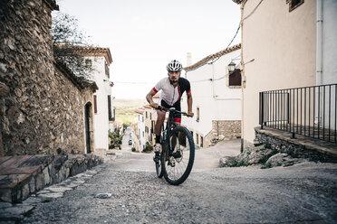 Mountain biker riding uphill in mountain village - JRFF000726