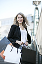 Portrait of smiling woman with several shopping bags - GDF001004