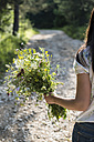 Back view of woman holding bunch of wildflowers - DEGF000818