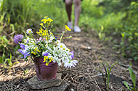 Small bucket with wildflowers on the ground - DEGF000821