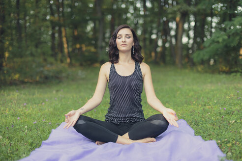 Croatia, Woman meditating in lotus position, yoga in nature - LCU000001