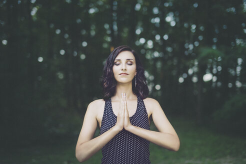 Young woman meditating with closed eyes in the forest, yoga in nature - LCU000007