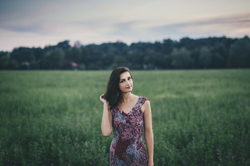 Portrait of a woman wearing a dress in a green field - LCU000010