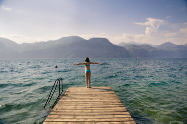 Italy, Brenzone, back view of girl standing on jetty - LVF004903