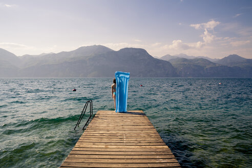 Italy, Brenzone, back view of girl standing with blue airbed on jetty - LVF004906
