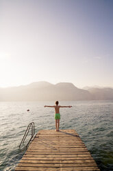 Italy, Brenzone, back view of boy standing on jetty - LVF004912