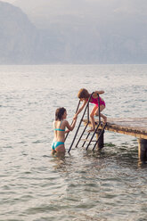 Italy, Brenzone, girl helping her little sister from jetty into the lake - LVF004915