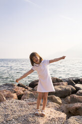 Italy, Brenzone, little girl with arms outstretched standing at lakeshore - LVF004918
