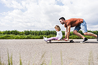 Father pushing daughter on skateboard - UUF007399