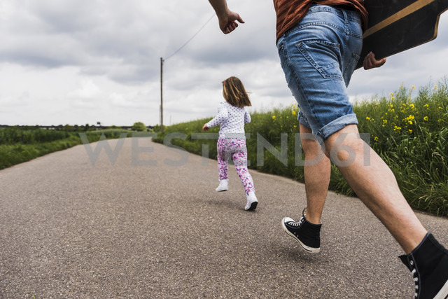 Father with skateboard and daughter running on country lane - UUF007405