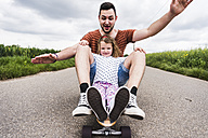 Daughter and father sitting on skateboard - UUF007408