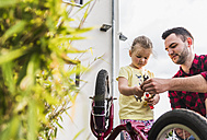 Father and daughter repairing bicycle together - UUF007417