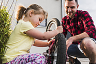 Father and daughter repairing bicycle together - UUF007420