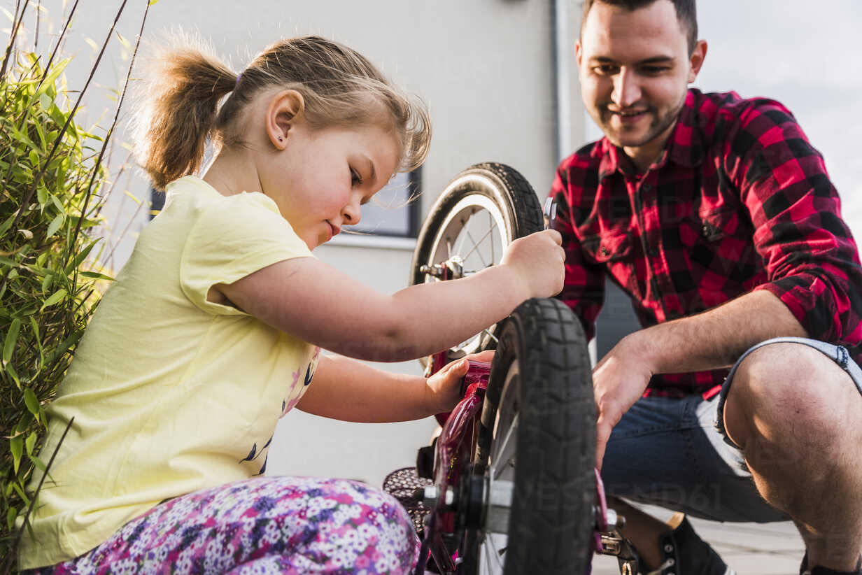 Father and daughter repairing bicycle together - UUF007420 - Uwe Umstätter/Westend61