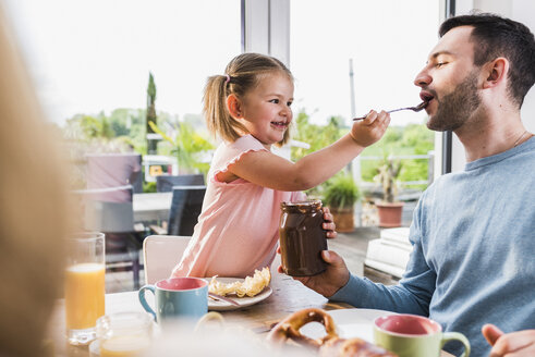 Father and daughter having breakfast together - UUF007426
