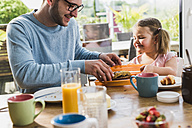 Father and daughter having breakfast together - UUF007438