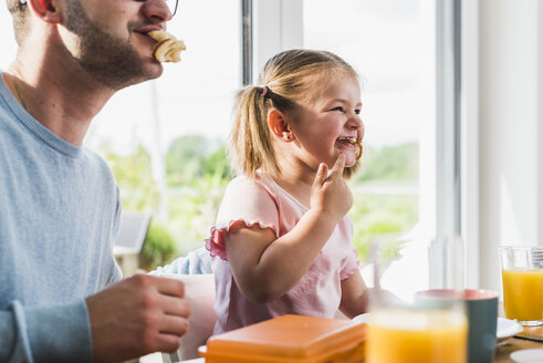 Playful father and daughter with food in mouth - UUF007441