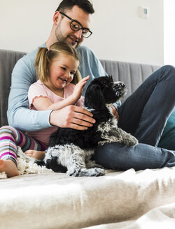 Father and daughter petting dog at home - UUF007444