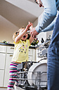 Playful daughter and father clearing dishwasher - UUF007447
