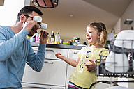 Playful daughter and father clearing dishwasher - UUF007450