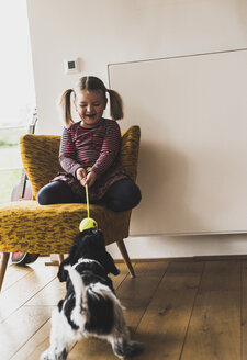 Girl playing with dog at home - UUF007453