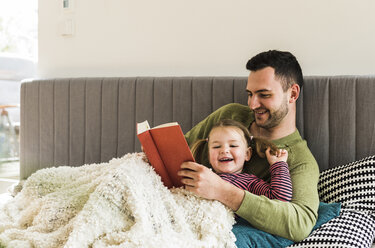 Happy father and daughter reading a book at home - UUF007456