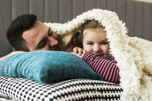 Father and daughter cuddling at home - UUF007459
