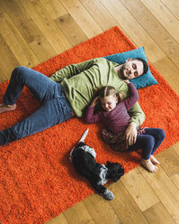 Father and daughter lying on carpet on the floor with dog - UUF007462