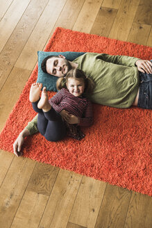Father and daughter lying on carpet on the floor - UUF007465