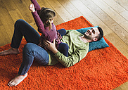 Playful father and daughter lying on carpet on the floor - UUF007468