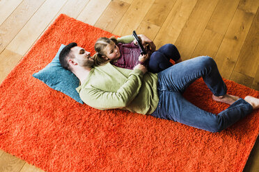 Father and daughter lying on carpet on the floor using digital tablet - UUF007471
