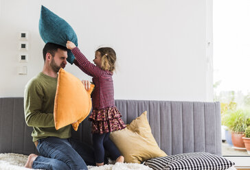 Father and daughter having a pillow fight - UUF007474