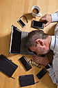 Overhead view of businessman lying on laptop surrounded by technology - MAEF011753