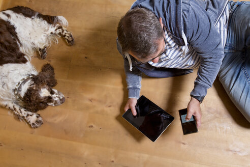 Overhead view of man using smartphone on the floor next to dog - MAEF011756
