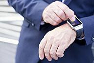 Close-up of businessman using smartwatch - MAEF011762