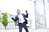 Enthusiastic businessman outside office building - MAEF011780