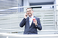 Smiling businessman on the phone outdoors - MAEF011783