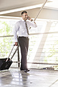 Businessman with luggage and cell phone on the move - MADF000886