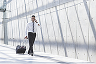 Businessman with luggage and cell phone on the move - MADF000889