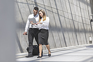 Businessman and businesswoman with digital tablet on the move - MADF000901
