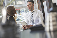 Laughing businessman with digital tablet looking at colleague in a cafe - MADF000919