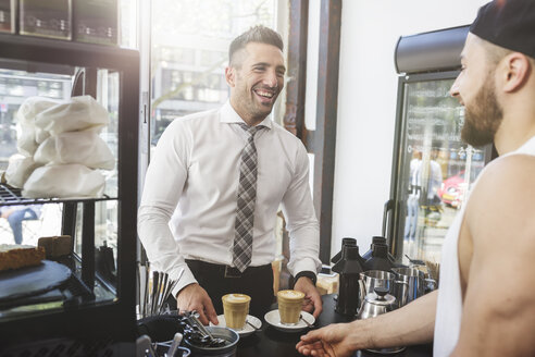 Laughing businessman in a cafe with barkeeper - MADF000925