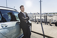 Businessman leaning against car at the airport - MADF000931