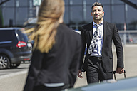 Smiling businessman with luggage at car park looking at woman - MADF000946