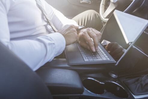 Businessman using digital tablet in car - MADF000949