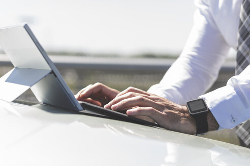 Businessman using digital tablet on car bonnet - MADF000952