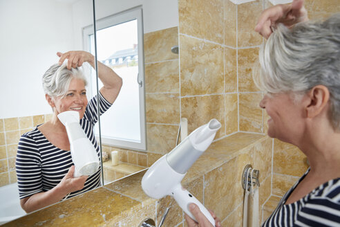 Smiling woman blow-drying her hair - FMKF002729
